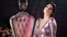 Beauty glamorous young brunette woman in evening pink sequins dress posing at luxury apartment stock footage