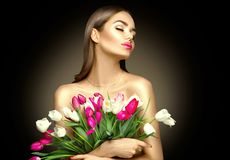 Beauty girl holding spring tulips. Beautiful woman receiving a bouquet of colorful tulips stock image
