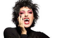 Beauty Gothic Girl. Vampire Makeup. Beautiful young woman screaming with fangs, wolf lenses and decorated nails Royalty Free Stock Image