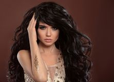 Beauty hair. Beautiful brunette model girl with shiny long curly. Hairstyle and makeup, golden art tattoo over brown background Royalty Free Stock Photos