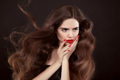 Beauty hair. Red manicure. Brunette girl with long shiny wavy ha Royalty Free Stock Images