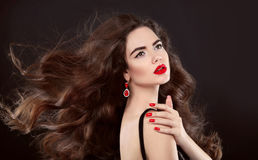 Beauty hair. Red manicure. Brunette girl with makeup and long sh Royalty Free Stock Image