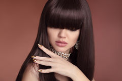 Beauty hair. Vogue Hairstyle. Fashion Manicure. Portrait of gorgeous young dark-haired woman. Sensual lips makeup. Golden polish. Manicured nails royalty free stock photography