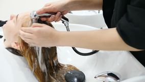 Beauty and hairstyle concept. Hairdresser washing woman ginger hair. Closeup shot of woman having her hair washed in. Sink in a luxury salon stock video