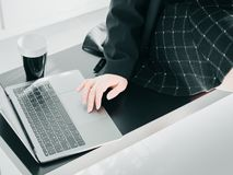 Beauty hand of asian business woman30s to 40s with black shirt. And skirt use computer laptop and put black coffee cup on table from coffee break time with soft Stock Photo