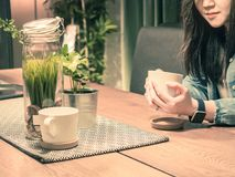 Beauty hand of asian hipster girl 25s to 35s with blue jacket. Jean during relax and drink coffee for wait her friend with soft focus decoratation background Royalty Free Stock Photo
