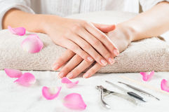 Beauty hands on the towel. Closeup shot of female hands with french manicure on a towel surrounded by petals and manicure set. Woman getting nail manicure Royalty Free Stock Photography