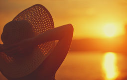 Beauty happy woman in her hat is back and admire sunset over sea Royalty Free Stock Photos