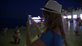 Beauty happy young girl taking picture of beautiful night city on smart phone. Selfie. Young tourist woman walking on night streets stock video