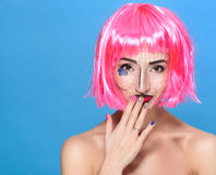 Beauty head shot. Cute Young woman with creative pop art make up and pink wig looking at the camera on blue background Stock Image
