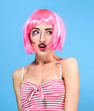 Beauty head shot. Surprised Young woman with creative pop art make up and pink wig looking at the camera on blue background Stock Photography