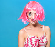 Beauty head shot. Young woman with creative pop art make up and pink wig looking at the camera on blue background Stock Photography