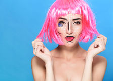 Beauty head shot. Young woman with creative pop art make up and pink wig looking at the camera on blue background Royalty Free Stock Photos