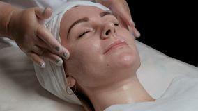 Beauty and health spa treatments. Woman on skin cleaning procedure in a beauty salon. Beautician in transparent gloves finishes so. Woman on skin cleaning stock video footage