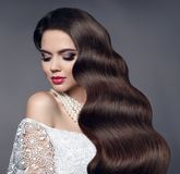 Beauty healthy hair. Glamour portrait of beautiful woman model w. Ith red lips and long shine hairstyle in wedding dress isolated on studio gray background Royalty Free Stock Photography