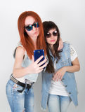 Beauty hipster girls with a headphones, make selfie on a phone. teenagers grimace Stock Image