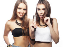 Beauty hipster girls with a microphone singing and having fun Royalty Free Stock Photo