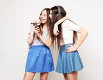 Beauty hipster girls with a microphone singing and take picture. Lifestyle, happiness, emotional and people concept: beauty hipster girls with a microphone Royalty Free Stock Photo