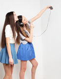 Beauty hipster girls with a microphone singing and take picture. Lifestyle, happiness, emotional and people concept: beauty hipster girls with a microphone Stock Photography