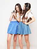 Beauty hipster girls with a microphone singing and take picture. Lifestyle, happiness, emotional and people concept: beauty hipster girls with a microphone Royalty Free Stock Image