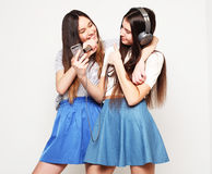 Beauty hipster girls with a microphone singing and take picture. Lifestyle, happiness, emotional and people concept: beauty hipster girls with a microphone Royalty Free Stock Images