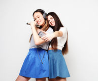 Beauty hipster girls with a microphone singing and take picture. Lifestyle, happiness, emotional and people concept: beauty hipster girls with a microphone Royalty Free Stock Photography