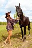 Beauty with horse. Image of smart female in hat and dress taking care of purebred horse outdoors stock image