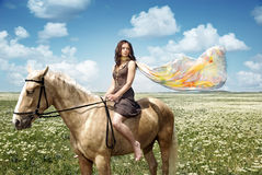 Beauty and horse. Lady with colorful scarf sitting on the serene horse Royalty Free Stock Image
