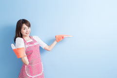 Beauty housewife show something. And wear gloves isolated on blue background Stock Photography