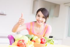 Beauty housewife in kitchen. Beauty housewife smile happily and show thumb up in the kitchen Royalty Free Stock Images