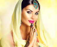 Beauty Indian girl with mehndi tattoos hold palms together. Beautiful Hindu exotic woman in sari and emerald oriental jewels looking in camera Stock Images