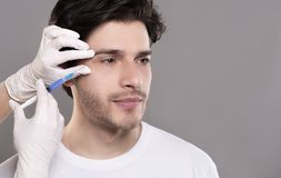 Millennial guy getting surgery filling of facial wrinkles. Beauty injection for men. Millennial guy getting surgery filling of facial wrinkles, empty space royalty free stock photos