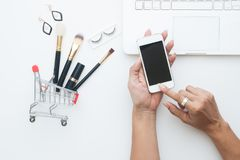 Beauty items, Brushes set in shopping cart with woman hand holding mobile phone, Top view shopping online. Concept royalty free stock images