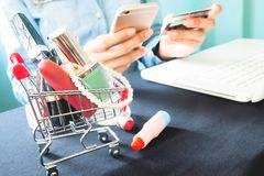 Beauty items in shopping trolley and woman using smartphone and. Credit card for online shopping, Lifestyle and technology Royalty Free Stock Image