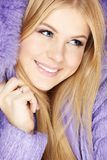 Beauty in a jacket. Beautiful blonde muffles up in the violet clothes, isolated Royalty Free Stock Photography