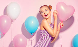Beauty joyful teenage girl with colorful air balloons having fun. Over pink background Stock Image