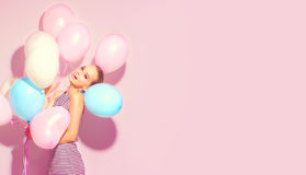 Beauty joyful teenage girl with colorful air balloons having fun. Over pink background stock photography
