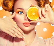 Beauty joyful teenage girl takes juicy oranges. Teen model girl with freckles, funny red hairstyle, yellow makeup and nails. On polka dots background stock photography