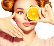 Beauty joyful teenage girl takes juicy oranges. Teen model girl with freckles, funny red hairstyle, yellow makeup and nails. On white background stock photos