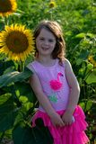 Beauty joyful young girl with sunflower enjoying nature and laughing on summer sunflower field. Sunflare, sunbeams, glow royalty free stock photo