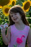 Beauty joyful young girl with sunflower enjoying nature and laughing on summer sunflower field. Sunflare, sunbeams, glow. View of Beauty joyful young girl with stock image