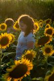 Beauty joyful young girl with sunflower enjoying nature and laughing on summer sunflower field. Sunflare, sunbeams, glow. View of Beauty joyful young girl with royalty free stock photo