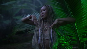 Beauty in the jungle. Beautiful woman with braids dancing near the palm tree in the jungle stock video