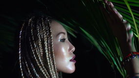 Beauty in the jungle. Closeup portrait of beautiful woman with braids posing near the palm tree in the jungle - video in slow motion stock video footage