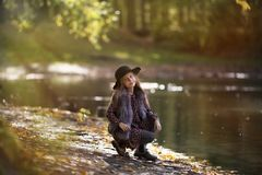 Beauty kid girl with long hair sitting near the river at the sunny evening stock photo