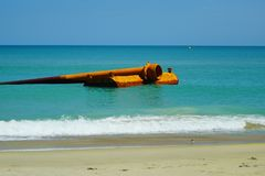 Kitty Hawk Beach Seascape with Floating Pipe. The  beauty of a Kitty Hawk, North Carolina beach as waves crash upon the shore with a backdrop of a rusted pipe Royalty Free Stock Image