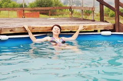 Beauty lady is swimming in a pool Royalty Free Stock Images