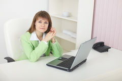 Beauty with laptop sits at table at light office Stock Photo