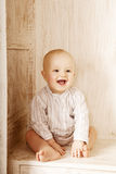 Beauty little baby sitting in the closet. Smiling child and inte Stock Photography