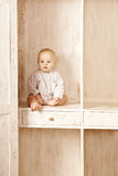 Beauty little baby sitting in the closet. Smiling child and inte Stock Images